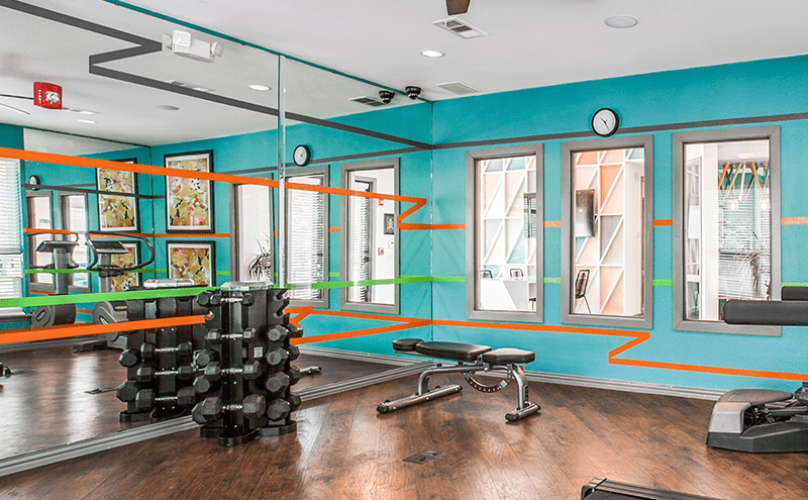 fitness center with modern colored walls, equipement and ample room