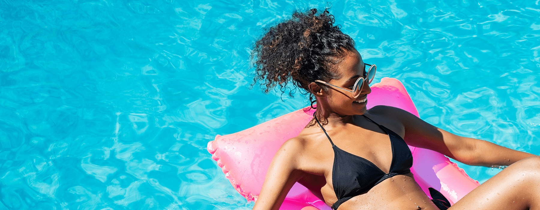 lifestyle image of a woman laying out on an inflatable chair in a swimming pool
